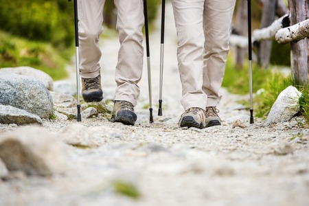 guy with walking stick: Close-up of legs of senior couple hiking at the beautiful mountains Stock Photo
