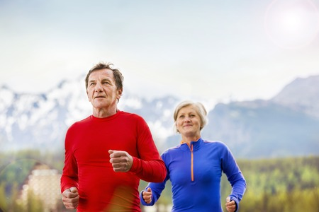 older men: Senior couple jogging round the tarn in beautiful mountains, hills and hotel in background Stock Photo