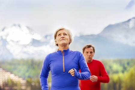 active woman: Senior couple jogging round the tarn in beautiful mountains, hills and hotel in background Stock Photo