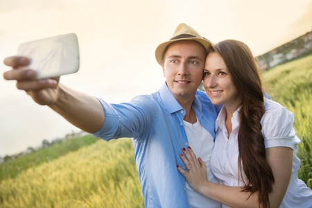 Happy young pregnant couple hugging in nature and taking selfie photo