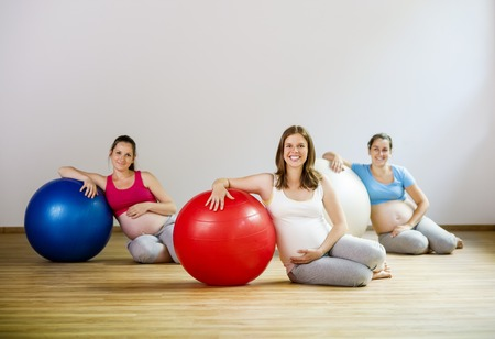 Young pregnant women doing relaxation exercise using a fitness ball Reklamní fotografie