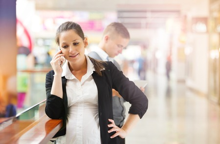 Businessman and businesswomen having a meeting in shopping mall  Woman is pregnant  photo