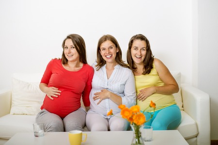 Three pregnant women sitting on sofa and posing photo