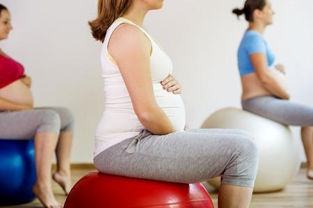 mujeres embarazadas: Mujeres embarazadas j�venes haciendo ejercicio con una pelota de fitness