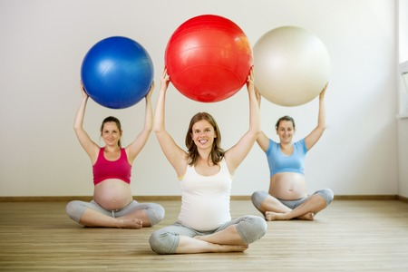Young pregnant women doing relaxation exercise using a fitness ball photo