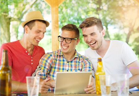non alcoholic beer: Three happy friends drinking and having fun with tablet in pub garden Stock Photo