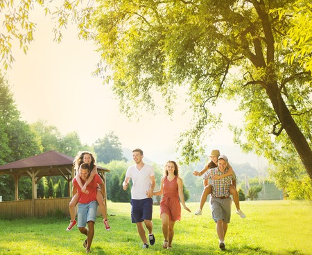 Group of five teenage friends having fun in park Stock Photo
