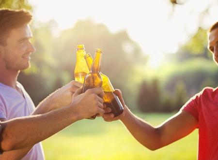 botellas de cerveza: Manos de los hombres clinnking botellas de cerveza en el parque