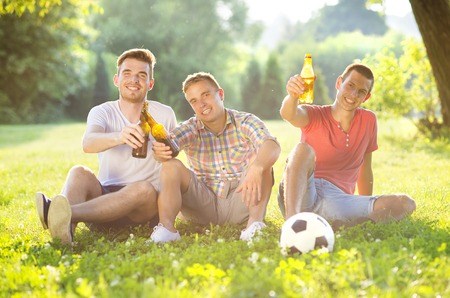 Three happy friends spending free time together in park sitting on grass, drinking beer and chatting photo