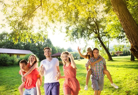 piggy back: Group of five teenage friends having fun in park Stock Photo