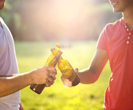 Hands of men clinnking beer bottles in park photo
