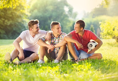 Three happy friends spending free time together in park sitting on grass and chatting