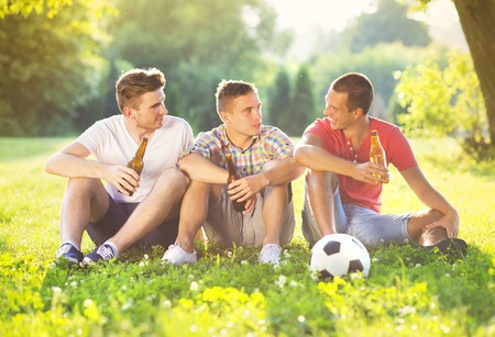 non alcoholic beer: Three happy friends spending free time together in park sitting on grass, drinking beer and chatting