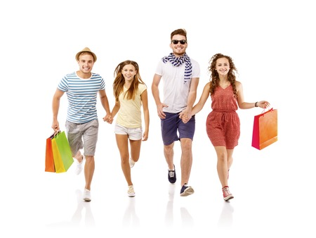 friends shopping: Group of happy young teenager students standing and smiling with shopping bags isolated on white background
