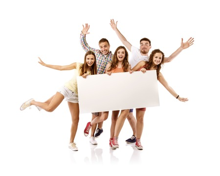 Group of happy young teenager students standing and smiling with blank placard board isolated on white background  photo