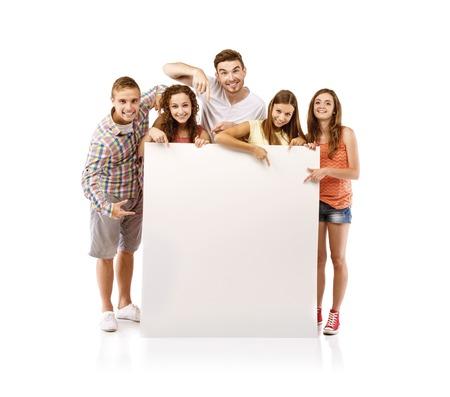 Groep gelukkige jonge tiener studenten staan en lachend met lege plakkaat bord geïsoleerd op witte achtergrond