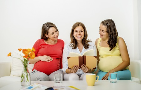 mothers group: Three pregnant women sitting on sofa and posing Stock Photo