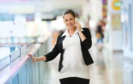 shopping centre: Busy pregnant woman talking on the phone in shopping centre Stock Photo