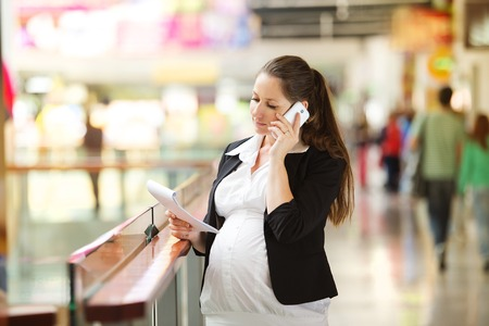 well dressed  holding: Busy pregnant woman talking on the phone in shopping centre Stock Photo