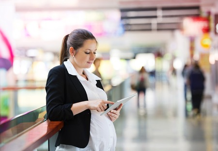 shopping centre: Busy pregnant woman using tablet in shopping centre