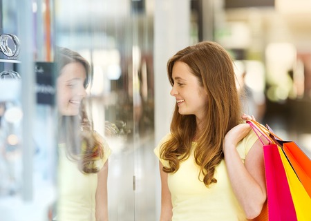 Smiling girl with shopping bags in shopping mall photo