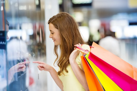 Smiling girl with shopping bags in shopping mall