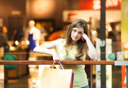 Girl in the shopping centre looking tired Stock Photo