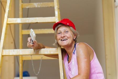 彼女を使用して新しい家に年配の女性の絵画の壁のはしご