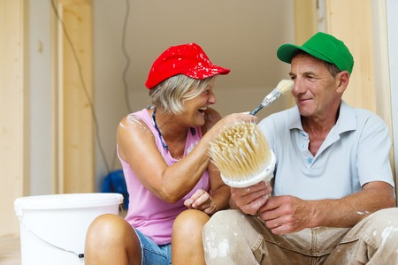 Active senior couple painting wall with brush in new house  They are having fun  photo