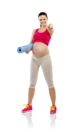 Studio portrait of a beautiful young pregnant woman holding mat ready for exercising, isolated on white background photo