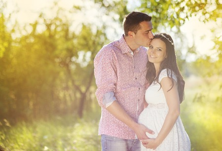 wives: Happy and young pregnant couple hugging in nature