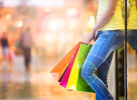 Tiempo de las compras, detalle de las piernas de la muchacha adolescente s con bolsas de compras en un centro comercial
