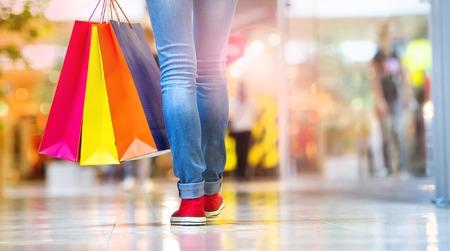 chicas de compras: Tiempo de las compras, de cerca de las piernas de ni�a adolescente con bolsas de la compra en el centro comercial