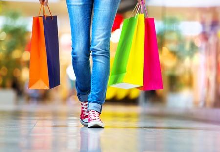 centro comercial: Tiempo de las compras, de cerca de las piernas de niña adolescente con bolsas de la compra en el centro comercial
