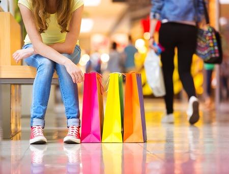 chicas compras: Tiempo de las compras, detalle de las piernas de la muchacha adolescente s con bolsas de compras en un centro comercial