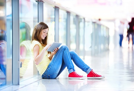 Pretty young girl sitting on the floor in a shopping mall and using her tablet photo
