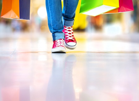 jeans: Shopping time, closeup of teenage girl legs with shopping bags at shopping mall Stock Photo