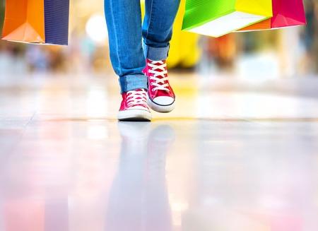 escarpines: Tiempo de las compras, de cerca de las piernas de niña adolescente con bolsas de la compra en el centro comercial