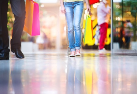 Detail of legs of young couple with bags in shopping mall photo