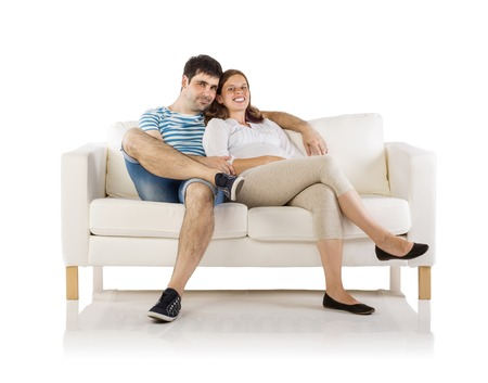 young wife: Beautiful young happy smiling pregnant couple sitting on sofa, isolated on white background