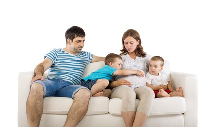 family couch: Portrait of the happy family with two children and pregnant mother sitting on sofa, isolated on white background Stock Photo