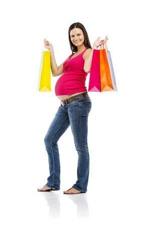 Studio portrait of beautiful young pregnant woman with shopping bags, isolated on white background photo