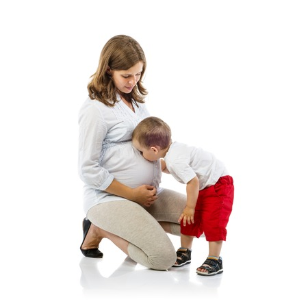 kissing pregnant belly: Portrait of the happy pregnant mother with her son kissing her belly, isolated on white background Stock Photo