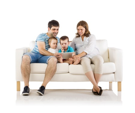family couch: Portrait of the happy family with two children and pregnant mother sitting on sofa and holding digital tablet, isolated on white background