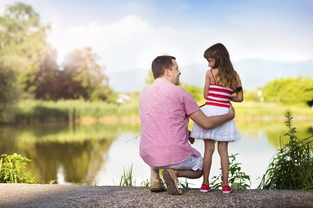 Happy young father fishing on the lake with his little daughter photo