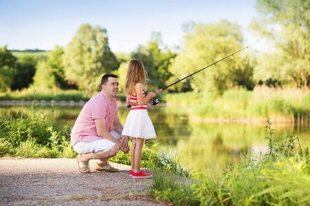 redes pesca: Feliz pesca del padre joven en el lago con su peque�a hija Foto de archivo