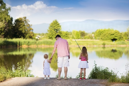 children pond: Happy young father fishing on the lake with his little daughters