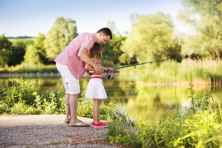 family activities: Happy young father fishing on the lake with his little daughter