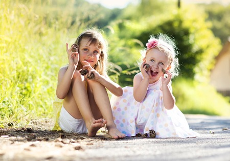 sittting: Two cute little sisters sittting and holding pine cones outdoors Stock Photo