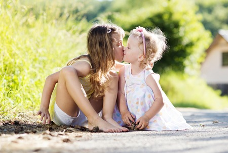 sittting: Two cute little sisters sittting and kissing in nature